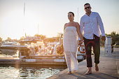 happy couple walking along harbor holding hands
