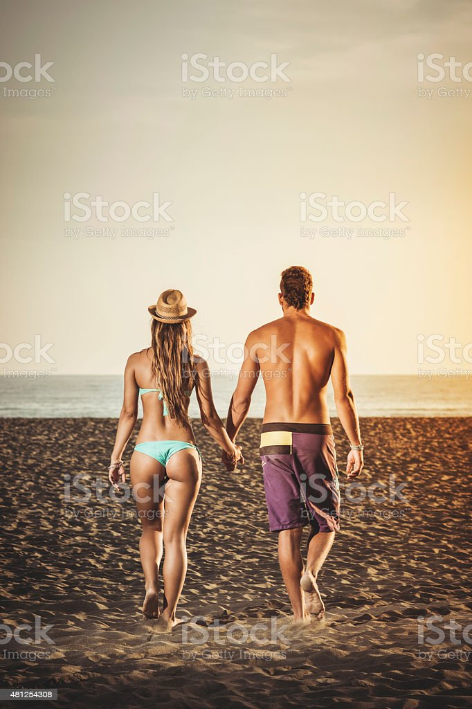 Happy couple walking at the beach stock photo