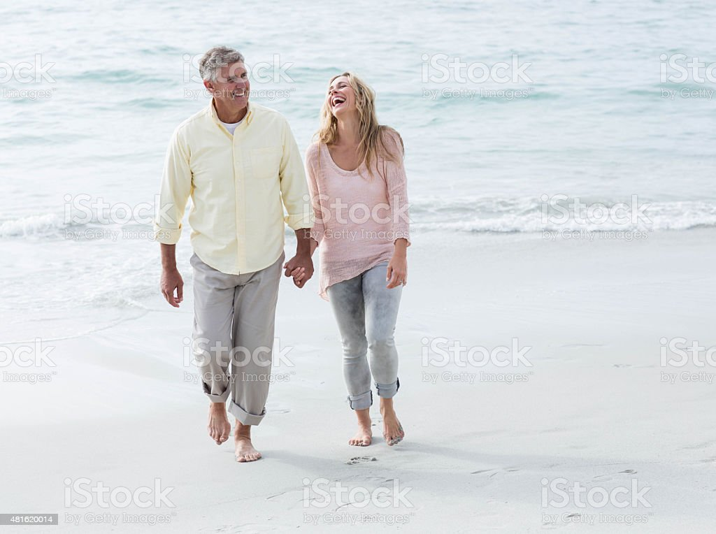 Happy couple walking by the sea stock photo