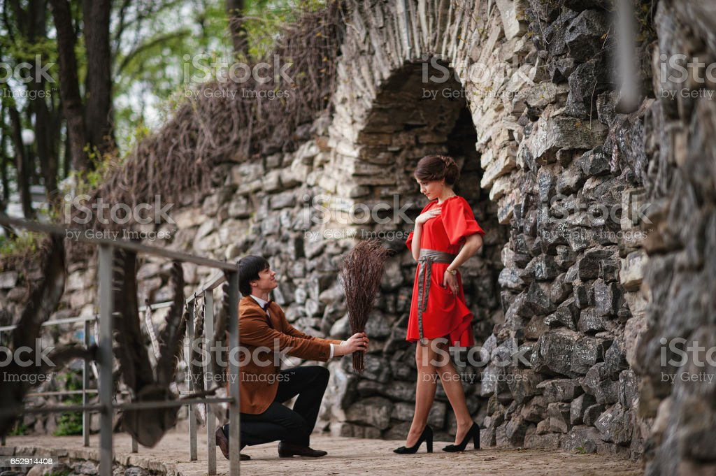 Happy couple walking in love at green park. Stylish man at velvet jacket and girl in red dress in love together stock photo