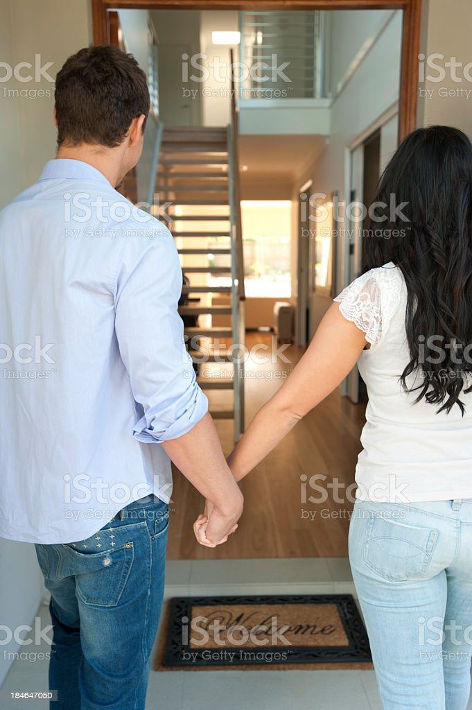 Happy couple walking into their new house royalty-free stock photo