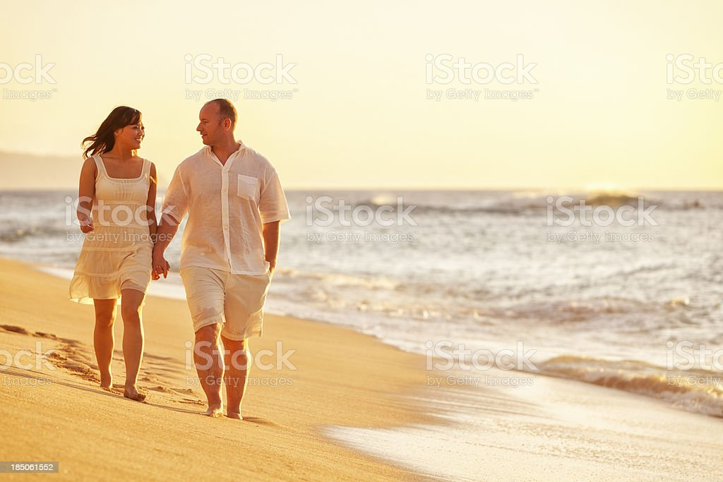 Happy Couple Walking on Hawaiian Beach at Sunset royalty-free stock photo