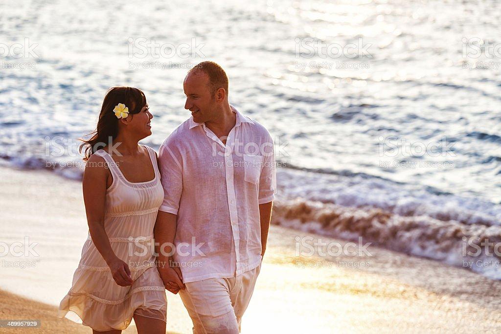 Happy Couple Walking on Hawaiian Beach at Sunset stock photo