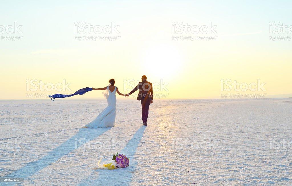 Happy couple walking on snow stock photo
