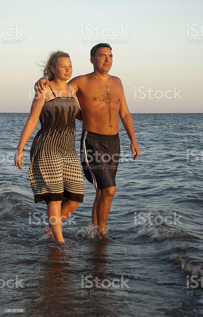 Happy couple walking on the beach royalty-free stock photo