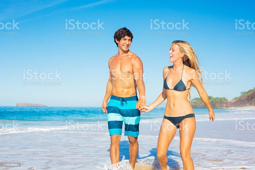 Happy Couple Walking on the Beach stock photo