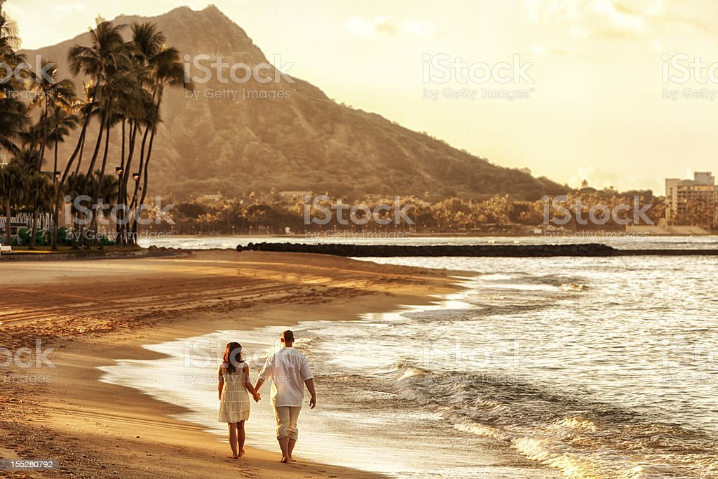 Happy Couple Walking on Waikiki Beach at Sunrise stock photo