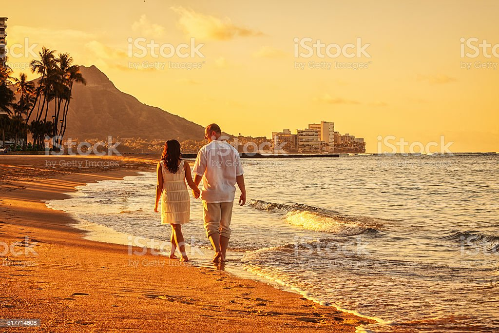 Happy Couple Walking on Waikiki Beach at Sunrise stock photo