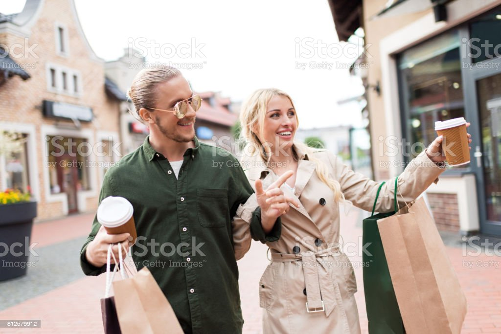 Happy couple walking with shopping bags and drinking coffee on street stock photo