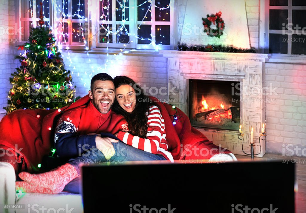 Happy couple watching TV at home stock photo