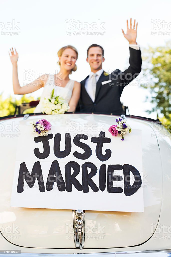 Happy Couple Waving In Convertible Car stock photo