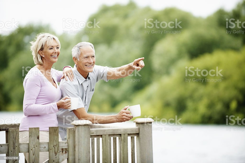 Happy couple with a man pointing at something interesting royalty-free stock photo