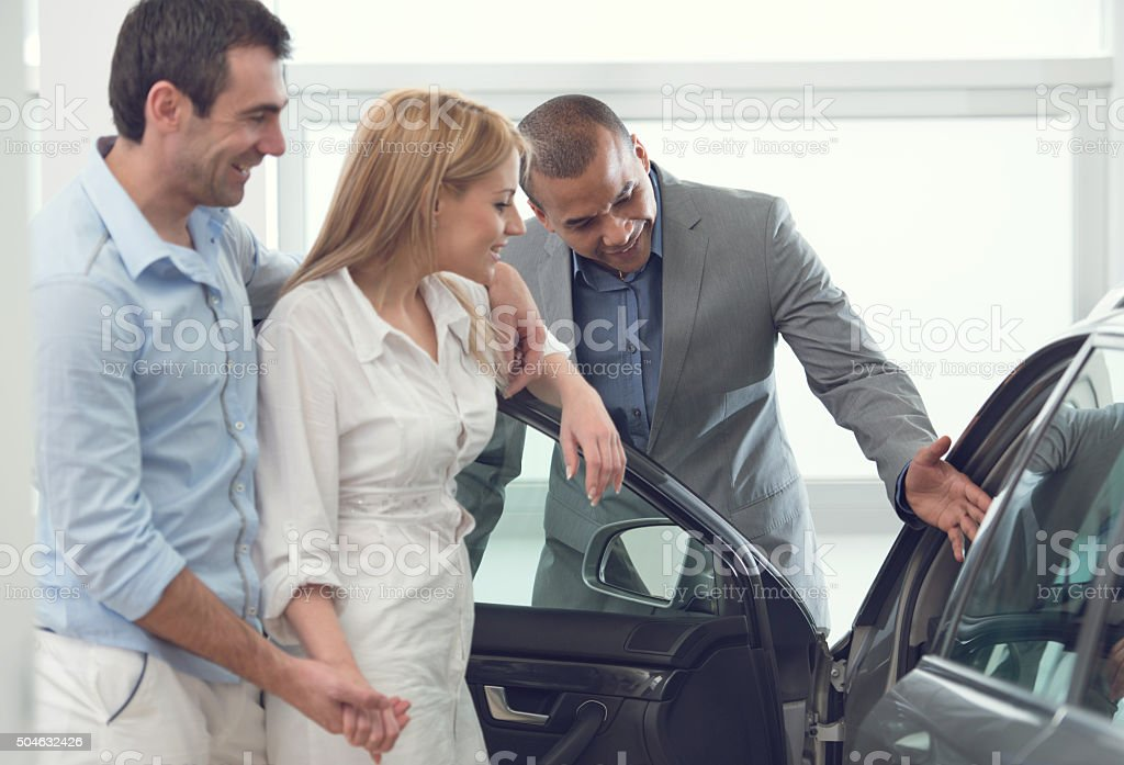 Happy couple with African American car salesperson. stock photo