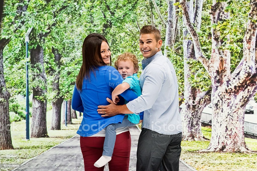 Happy couple with baby and looking at camera stock photo