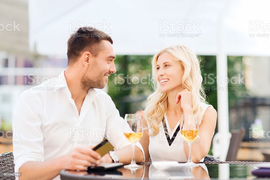 happy couple with bank card and bill at restaurant stock photo