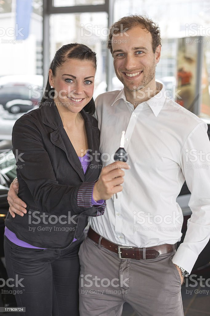 Happy couple with car key in dealership royalty-free stock photo