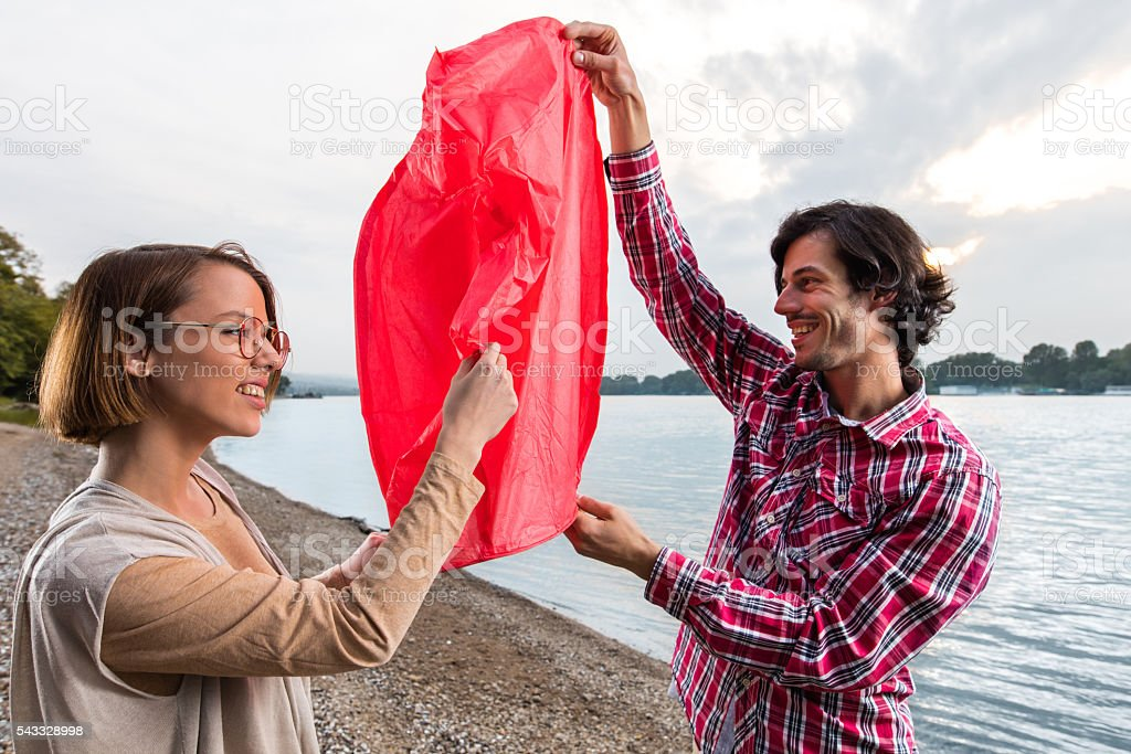Happy couple with Chinese lantern on the beach. stock photo