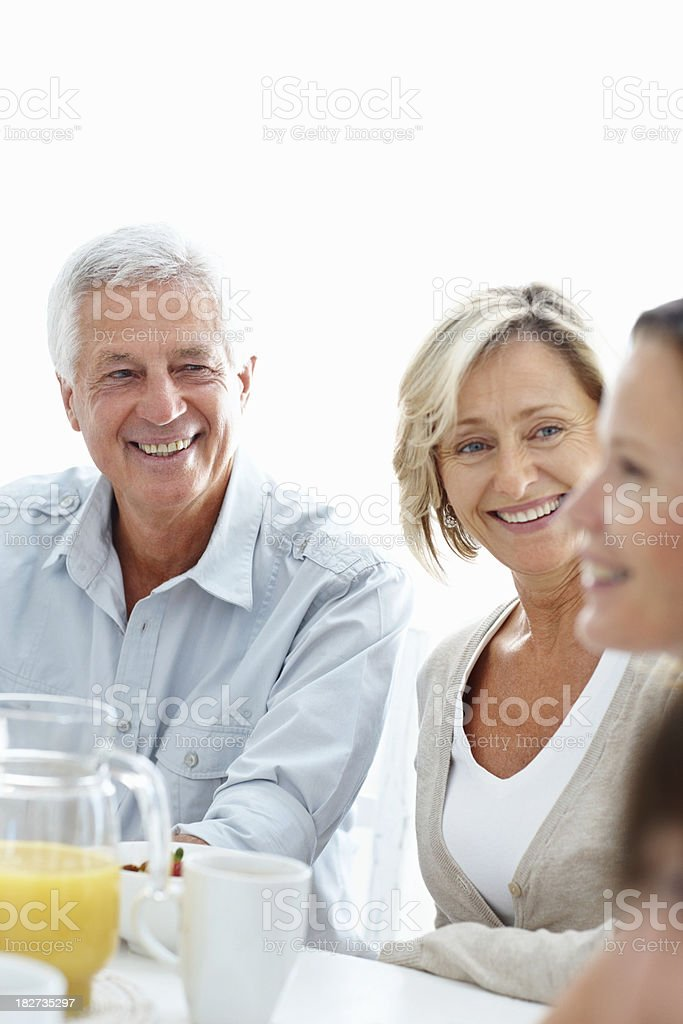 Happy couple with daughter sitting at breakfast table royalty-free stock photo