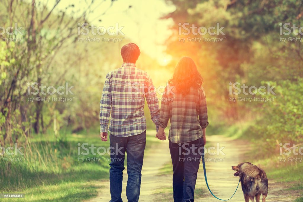 Happy couple with dog walking on rural road at sunset. stock photo