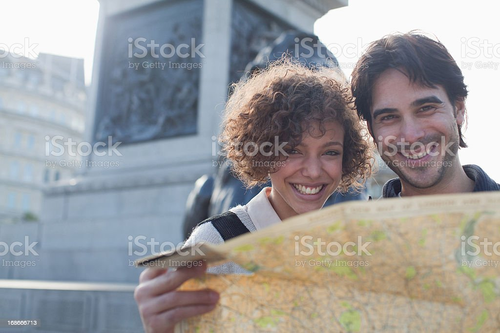 Happy couple with map below monument royalty-free stock photo