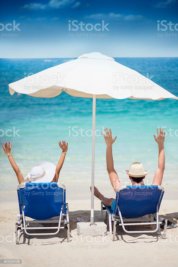 Happy Couple with Raised Hands in Tropical Beach Paradise stock photo