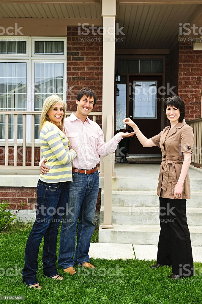 Happy couple with real estate agent stock photo