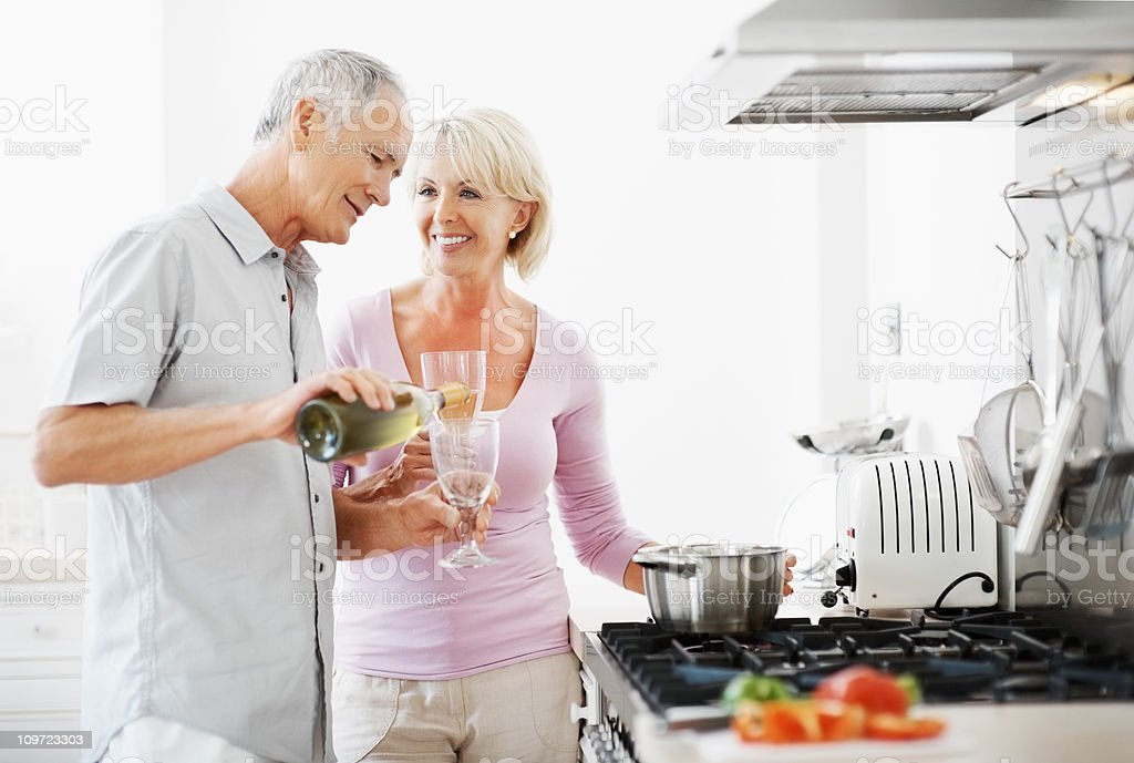 Happy couple with senior man pouring champagne in his glass stock photo