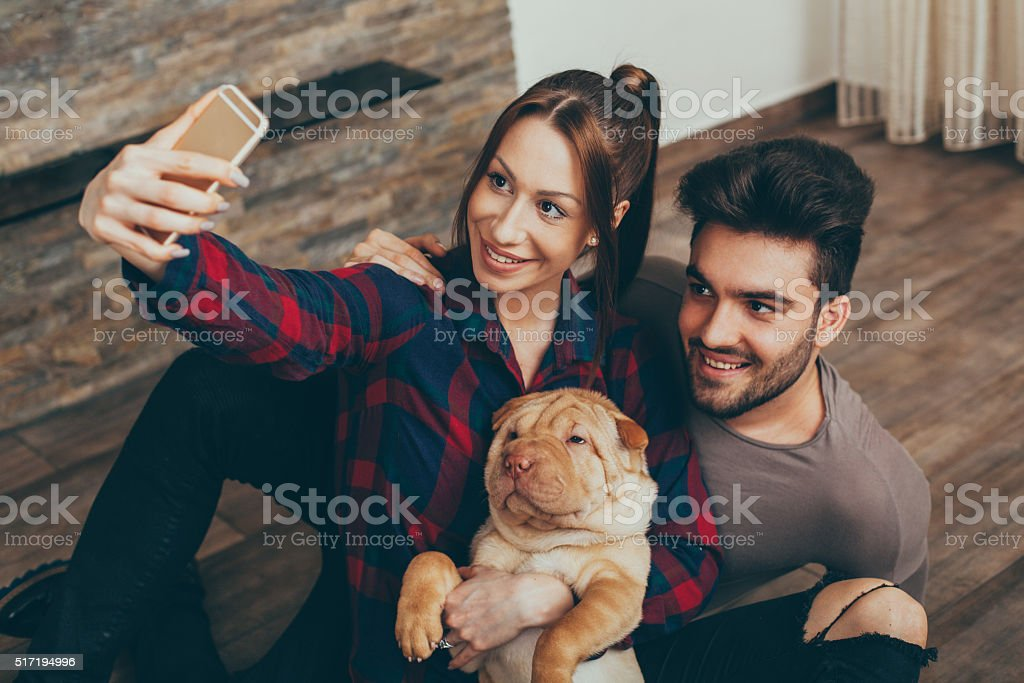 Happy couple with Shar Pei puppy taking selfie stock photo