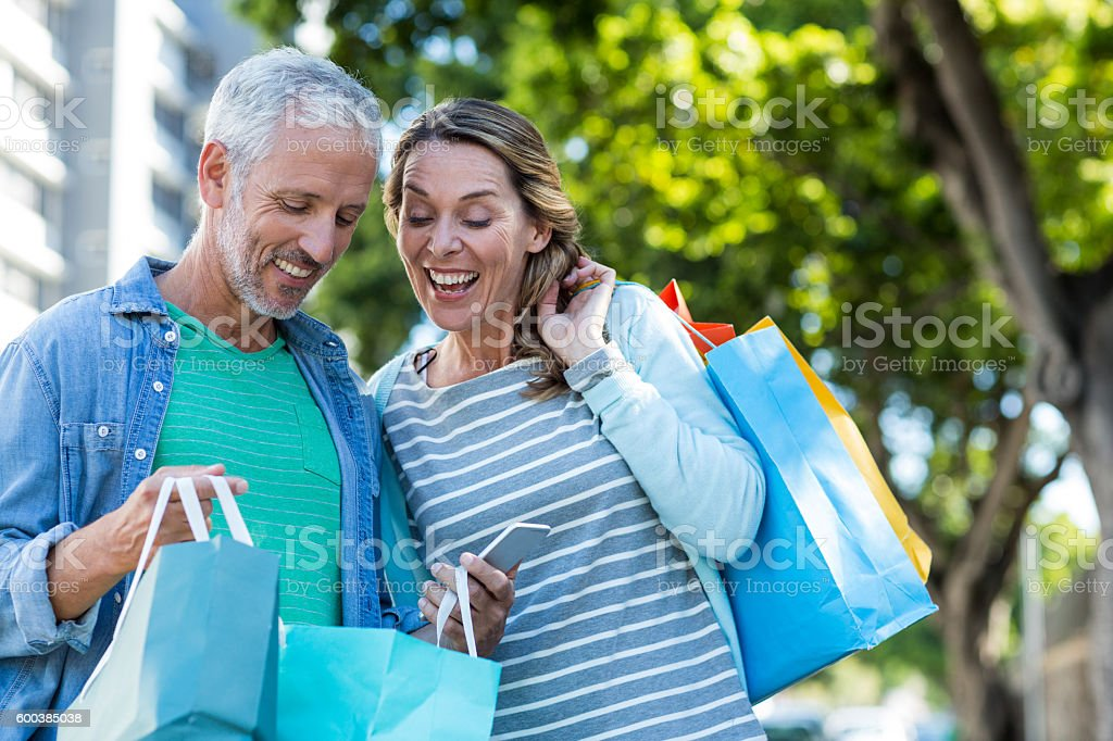 Happy couple with shopping bags in city stock photo
