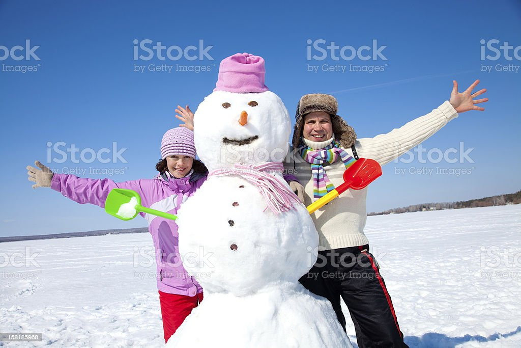 Happy couple with snowman royalty-free stock photo
