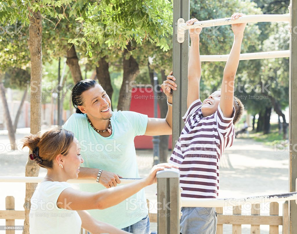 Happy couple with teenage son  training on pull-up bar stock photo