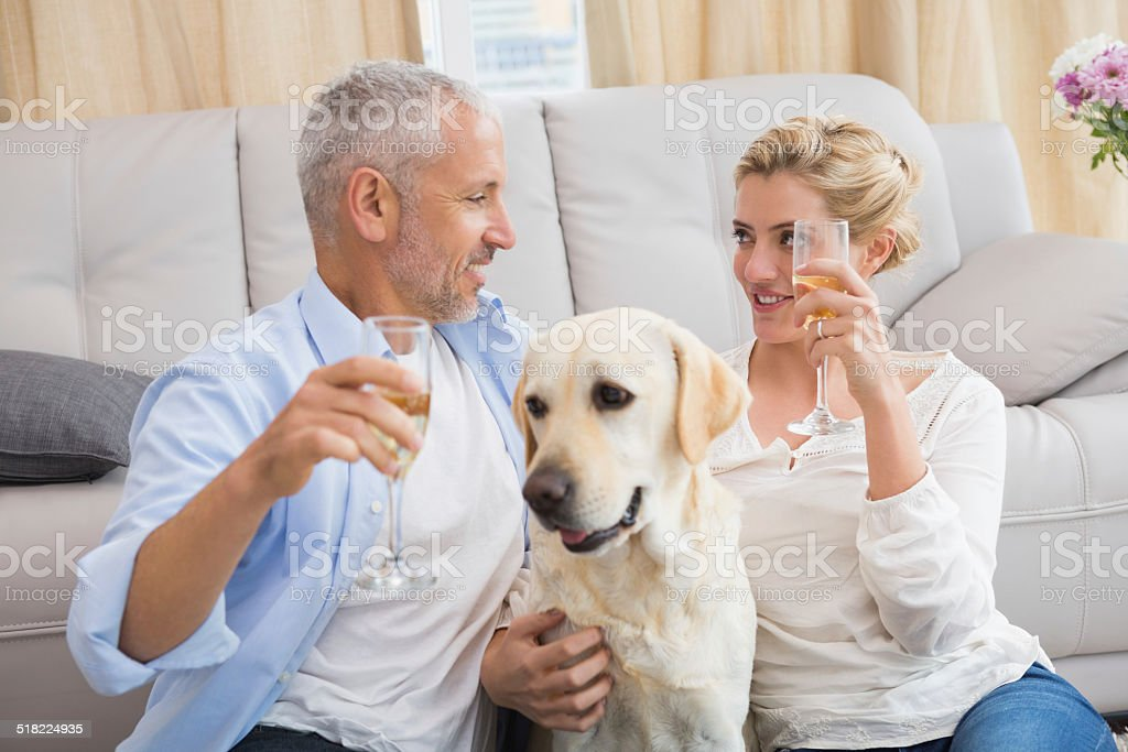 Happy couple with their pet dog drinking champagne stock photo