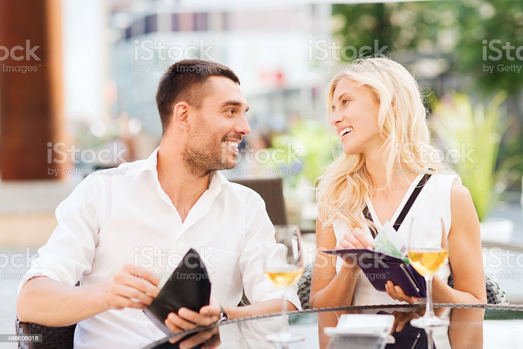 happy couple with wallet paying bill at restaurant stock photo