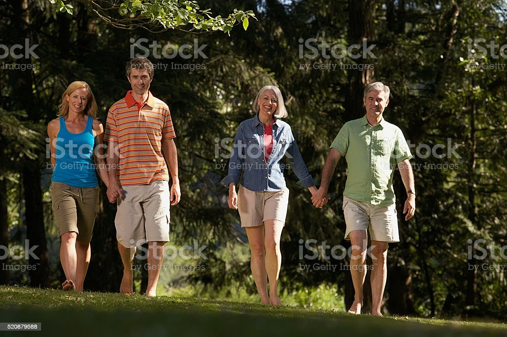 Happy couples walking in a park stock photo