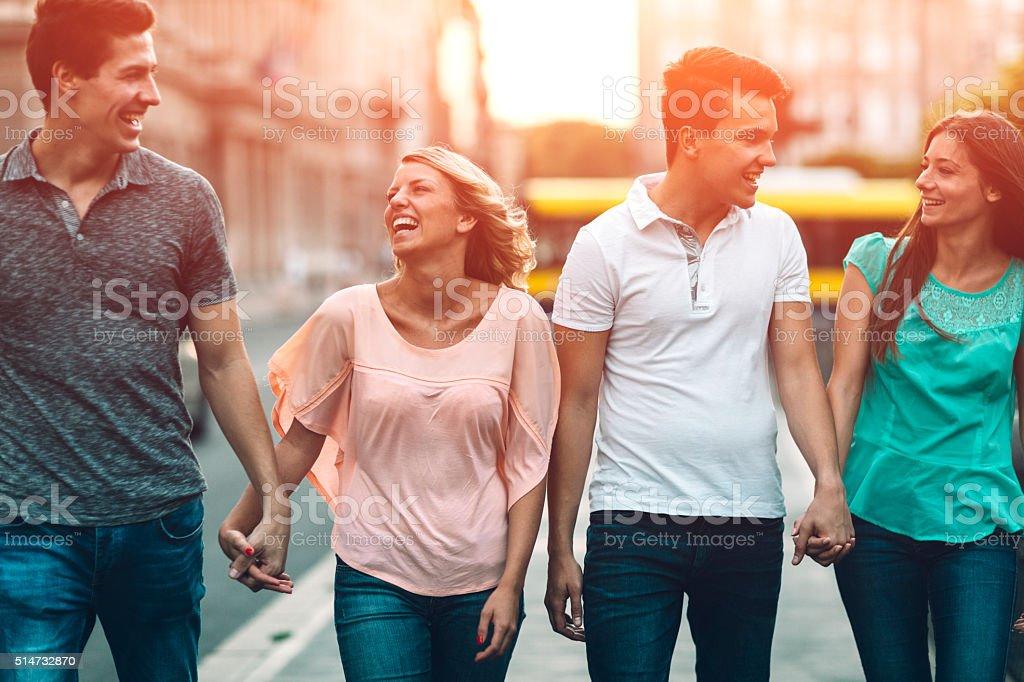 Happy Couples Walking In City. stock photo