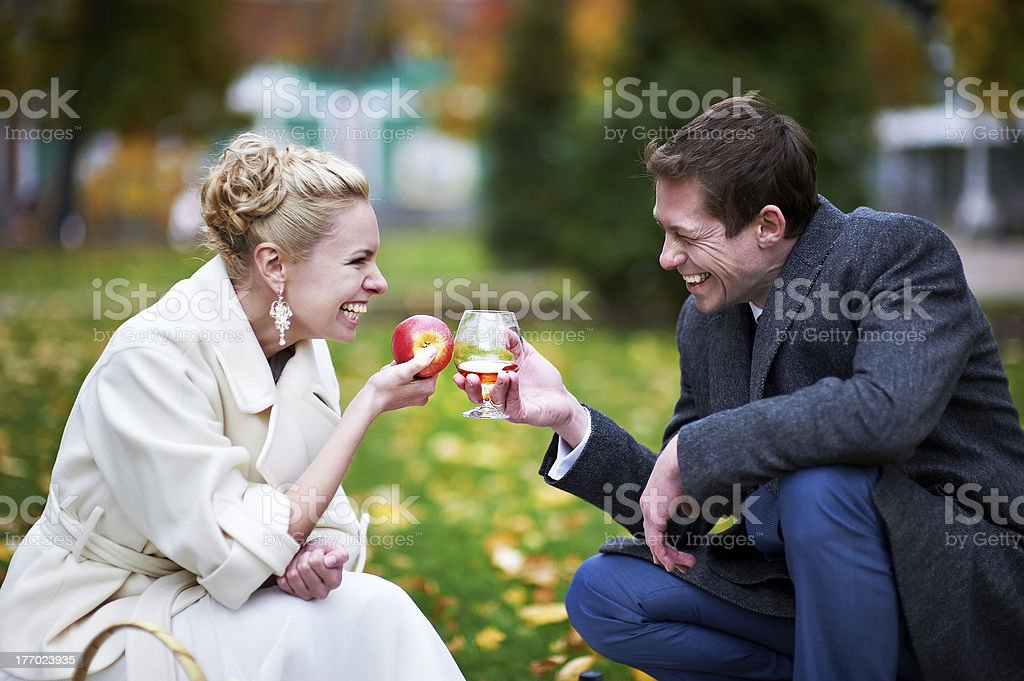 Happy couples with glass of brandy and red apple royalty-free stock photo