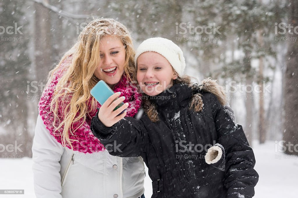Happy cousins take a selfie in a snow storm stock photo