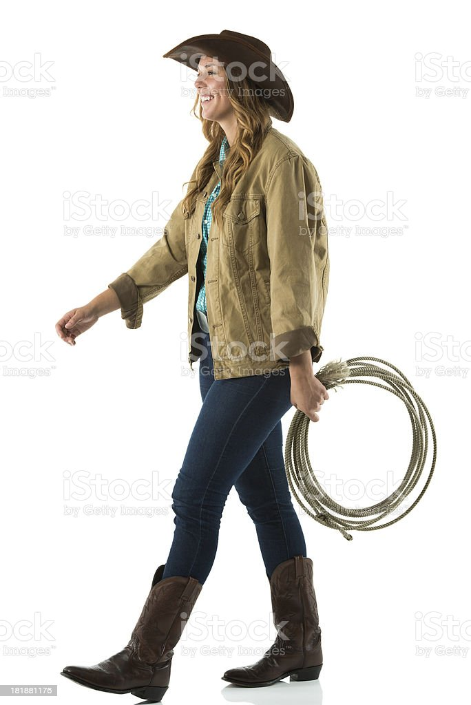 Happy cowgirl walking with lasso stock photo