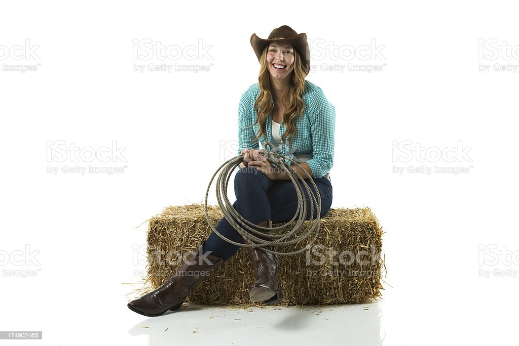 Happy cowgirl with lasso sitting on hay royalty-free stock photo