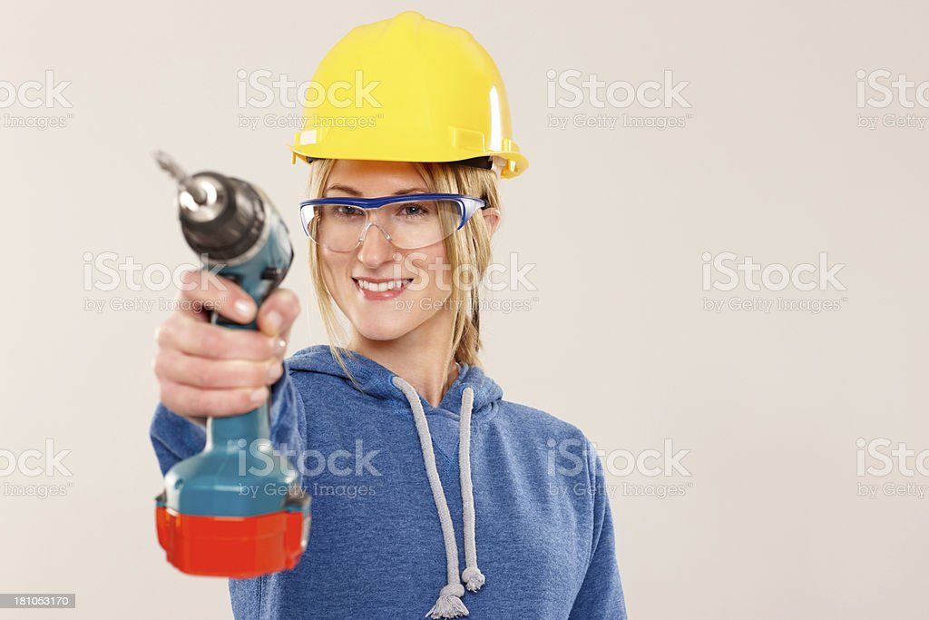 Happy craftswoman with a power drill in front royalty-free stock photo