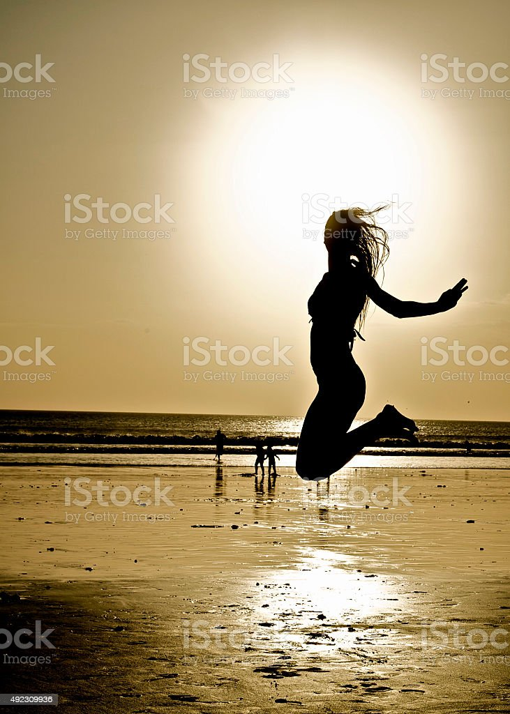 Happy crazy jumping girl on beach. Lucky Holidays. Positive emotion. stock photo