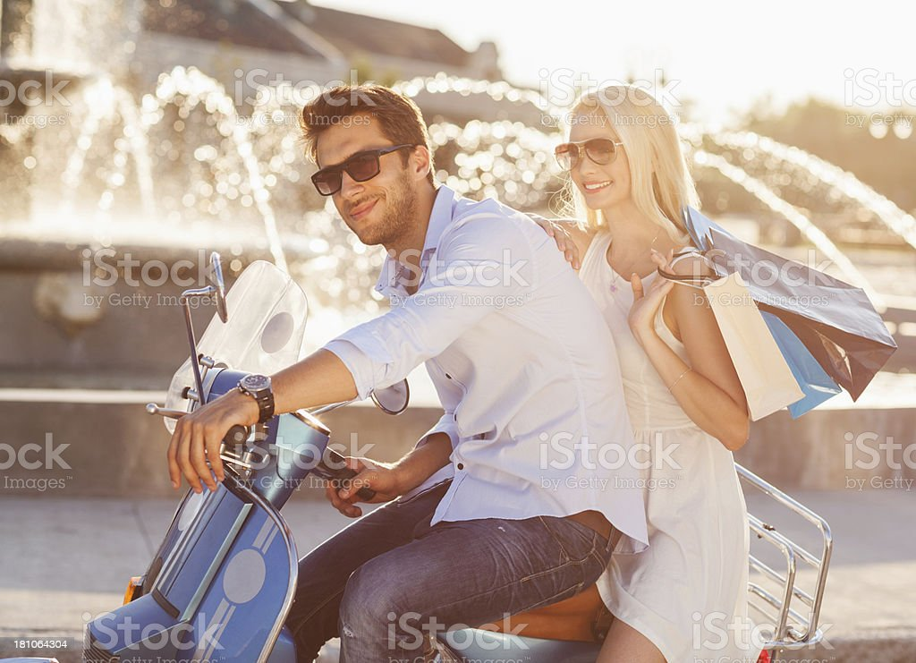 Happy cuple on scooter enjoying shopping royalty-free stock photo