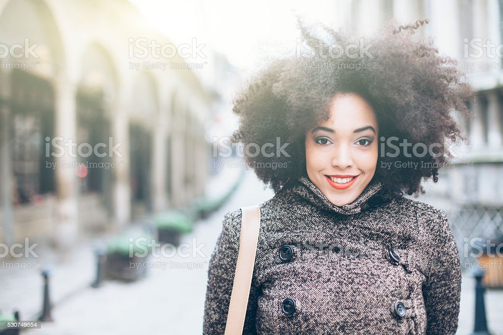 Happy curly young woman in front of an ancient  building stock photo