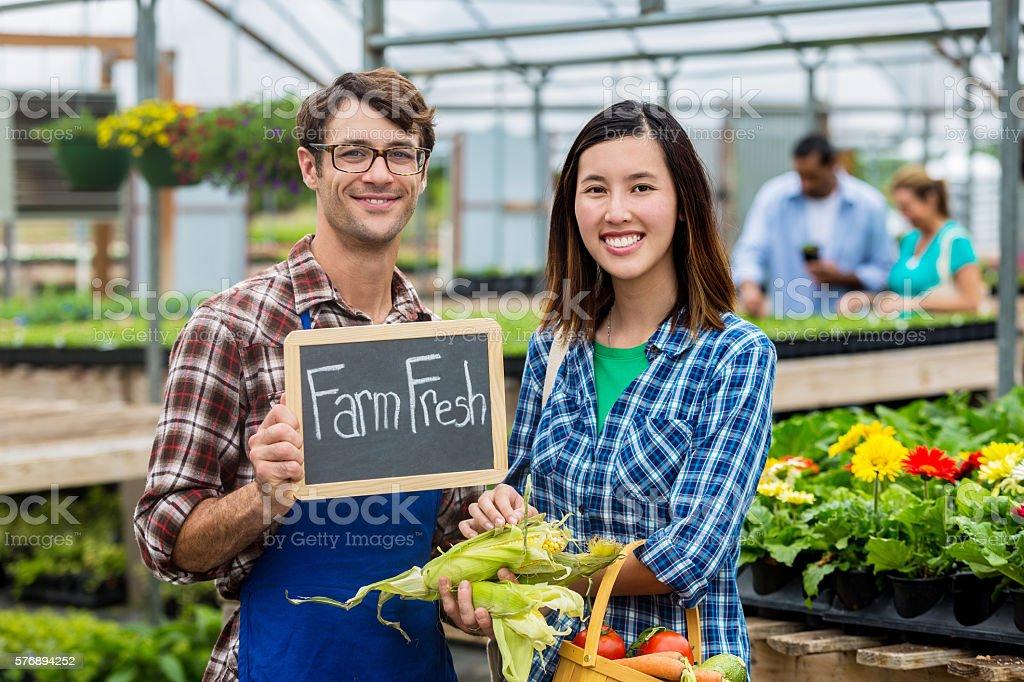 Happy customer and farmer at market with 'farm fresh' sign stock photo