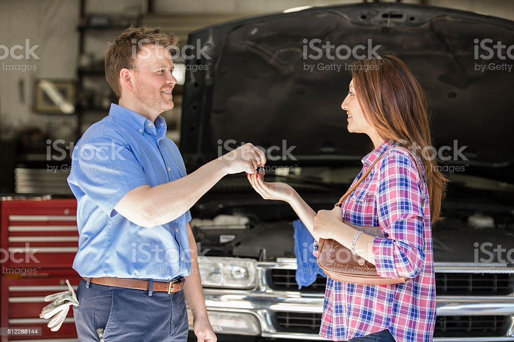 Happy customer gets keys. Satisfied with auto mechanic's great service. stock photo
