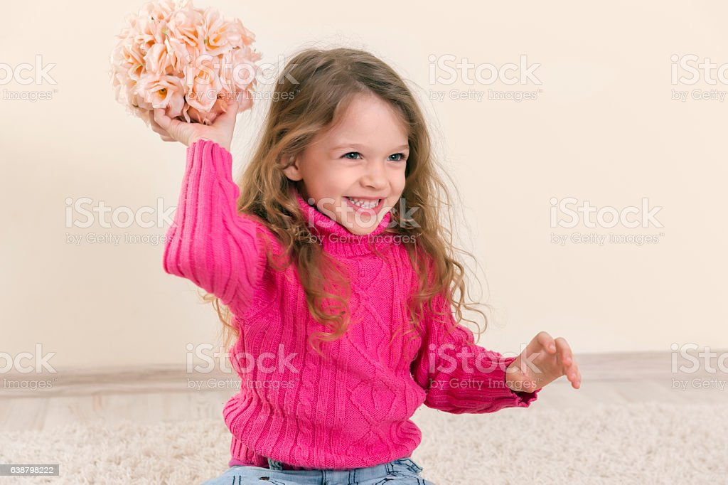 Happy cute blonde girl playing with flowers stock photo
