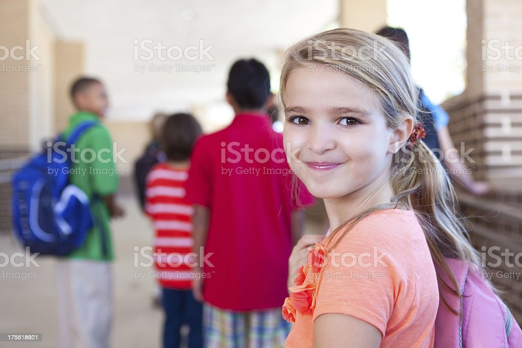 Happy cute elementary age girl outside after school stock photo