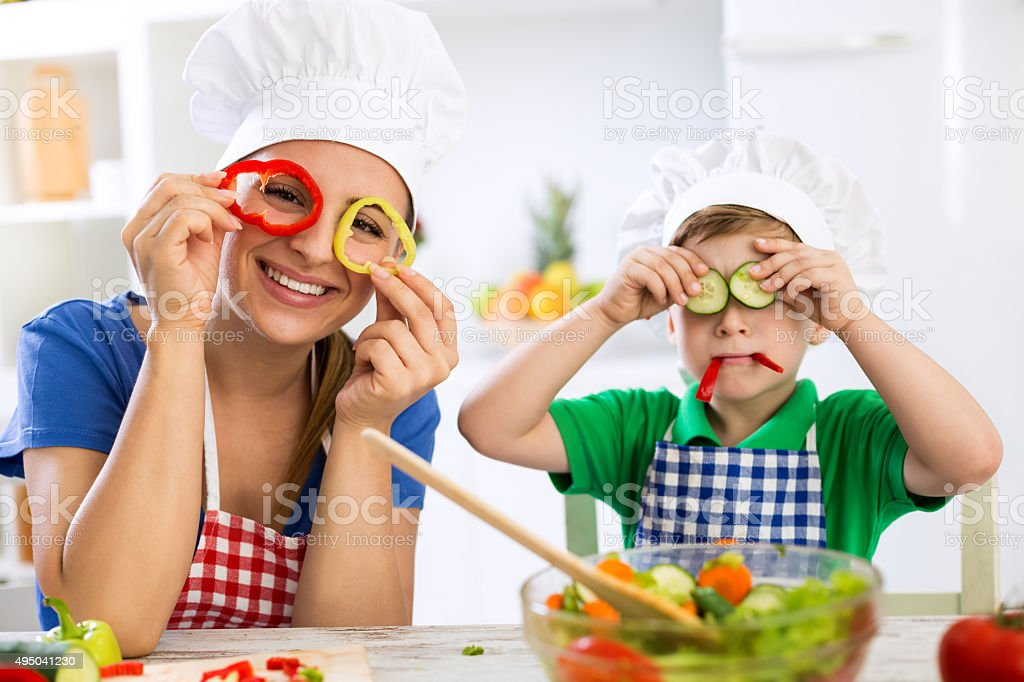 Happy cute family have fun in the kitchen with vegetables stock photo