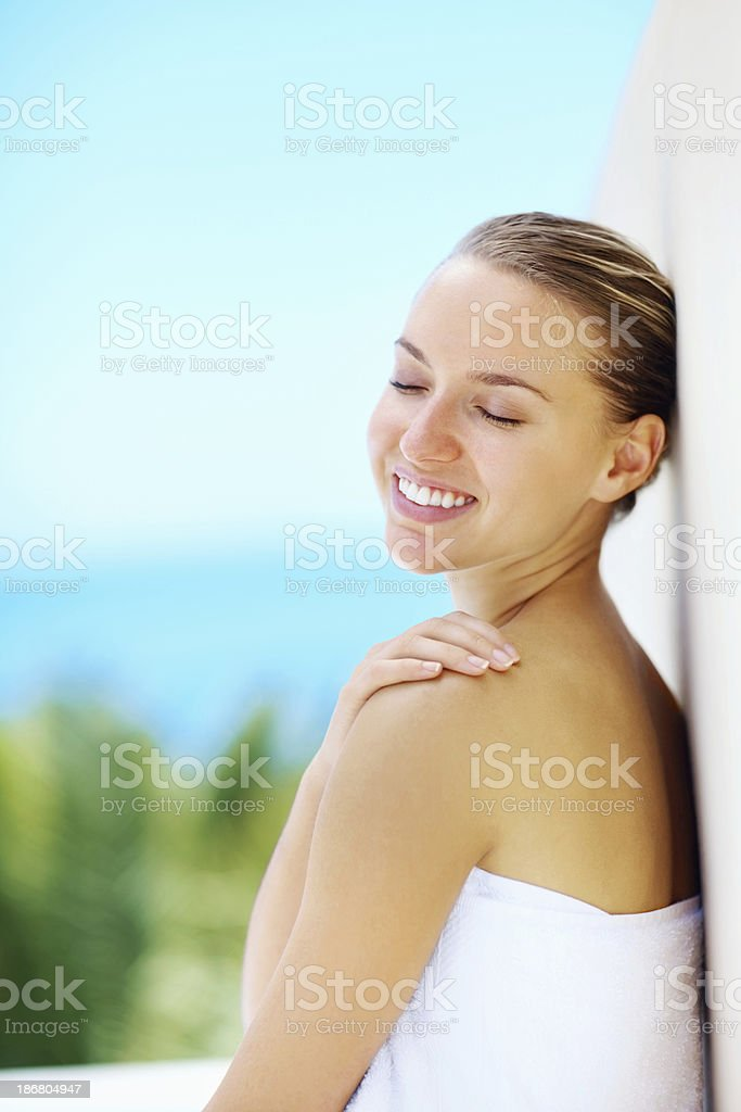 Happy cute female in towel leaning against a wall outside royalty-free stock photo