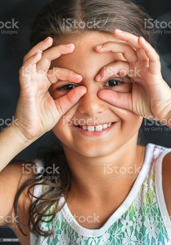 Happy  cute girl looking at camera through fingers royalty-free stock photo